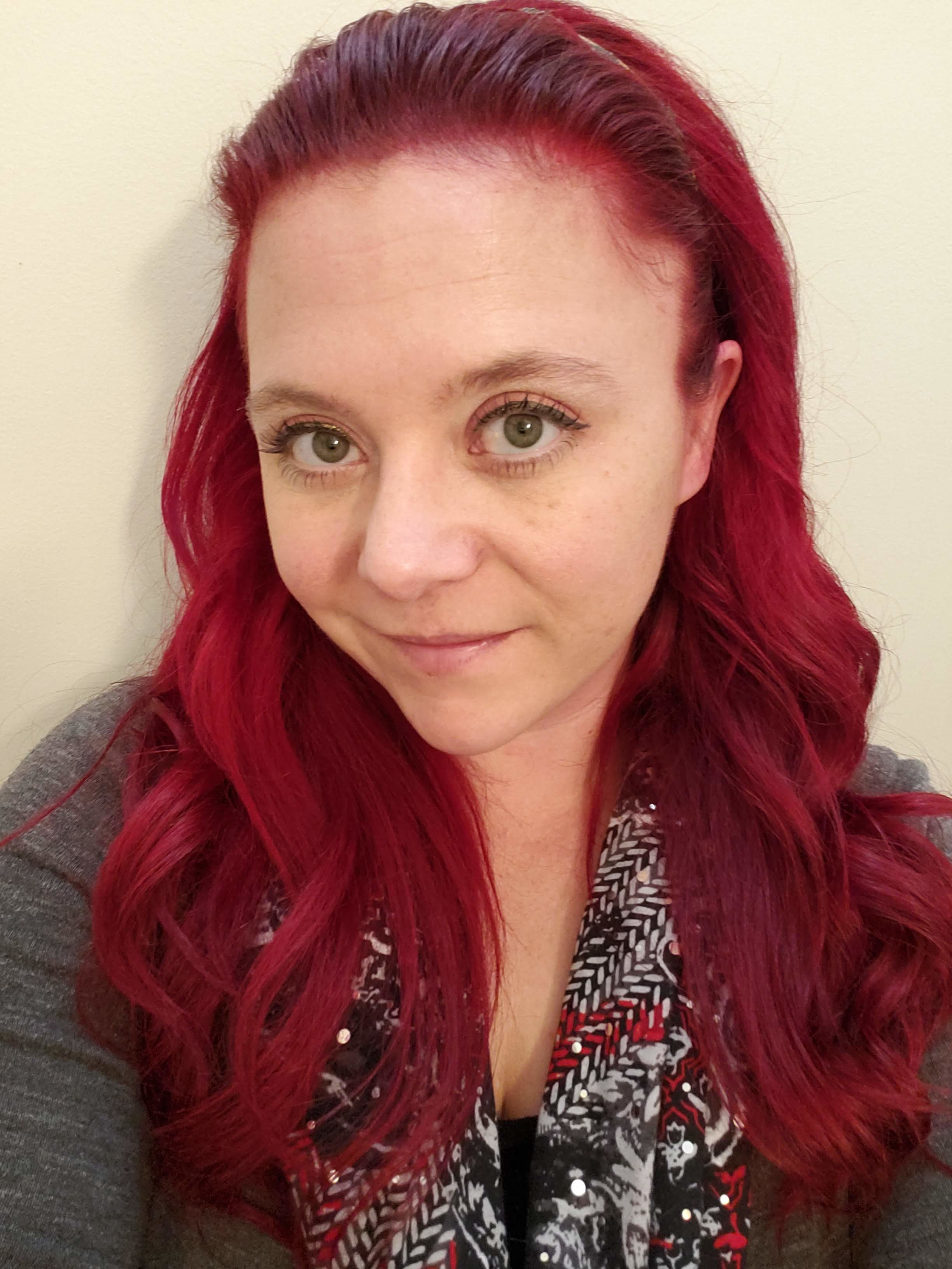 Profile picture of me with red hair, face forward, gray sweater and a printed scarf.